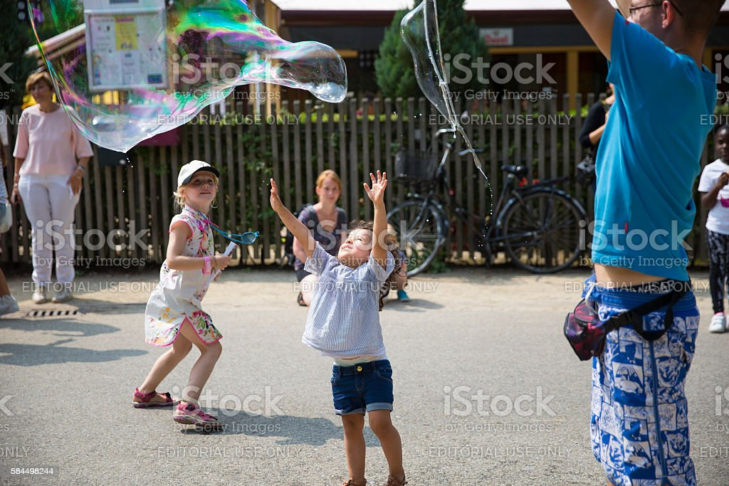children running after and bursting bubbles stock photo