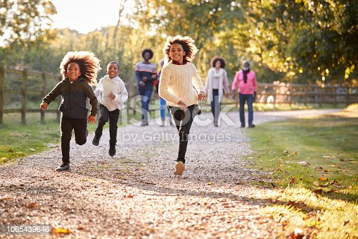 Children Running Ahead As Multi Generation Family Enjoy Autumn Walk In Countryside Together