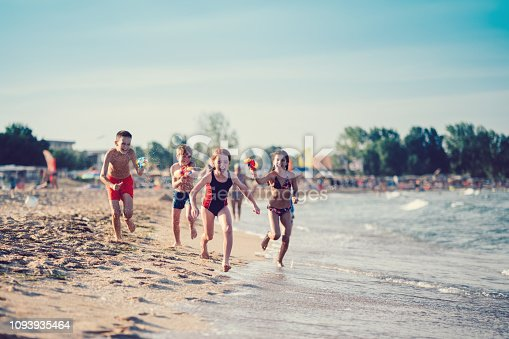 Group of kids playing with water pistols on beach holiday