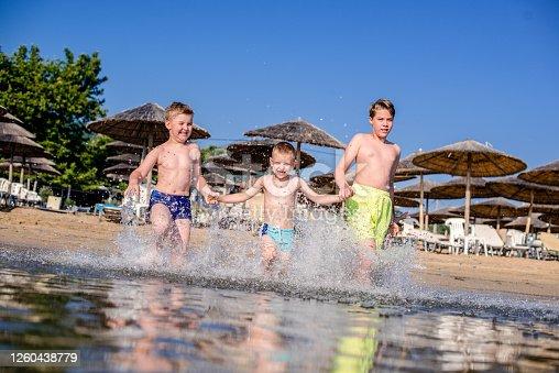 Children running into the sea and splashing water