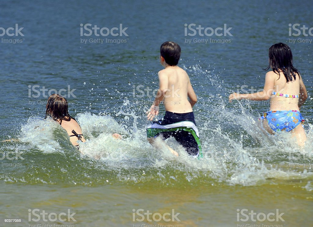 Children running into water royalty-free stock photo