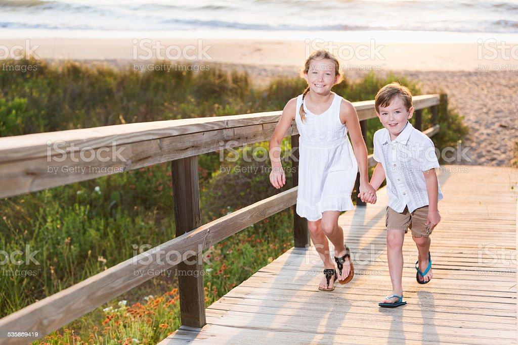 Crianças correndo na praia boardwalk - foto de acervo