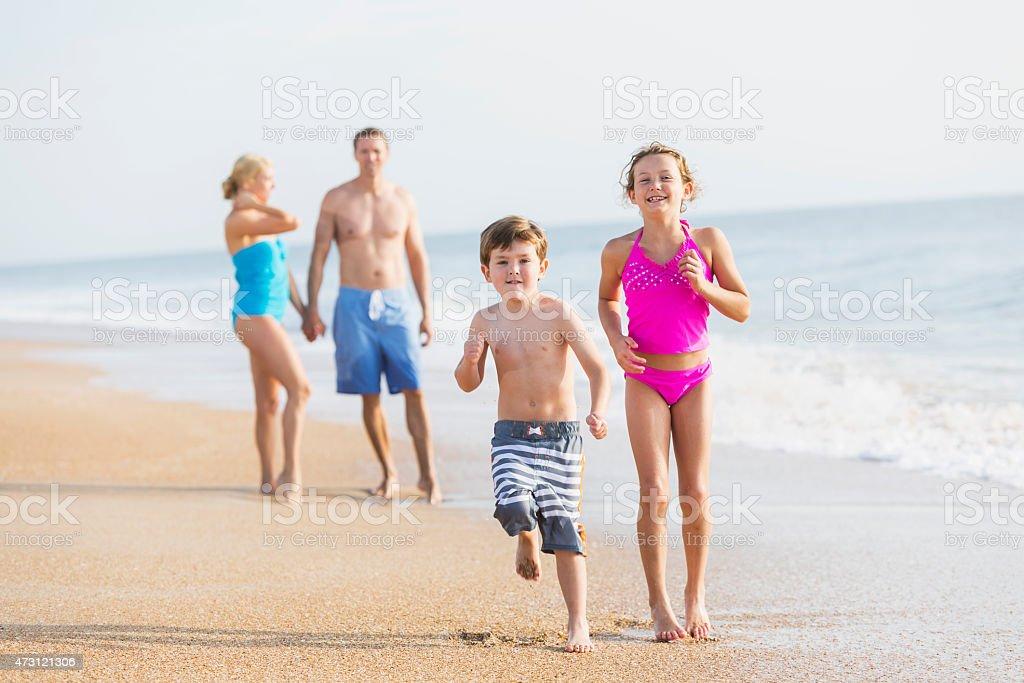 Children running on beach, parents watching stock photo