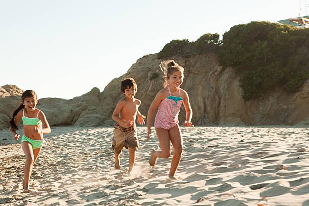 Children running on beach stock photo