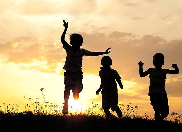 kinder laufen auf wiese bei sonnenuntergang - gegenlicht stock-fotos und bilder