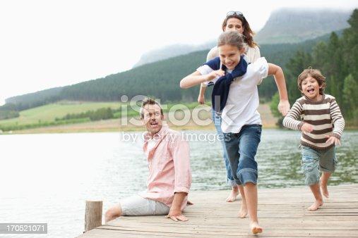 istock Children running on pier by lake 170521071