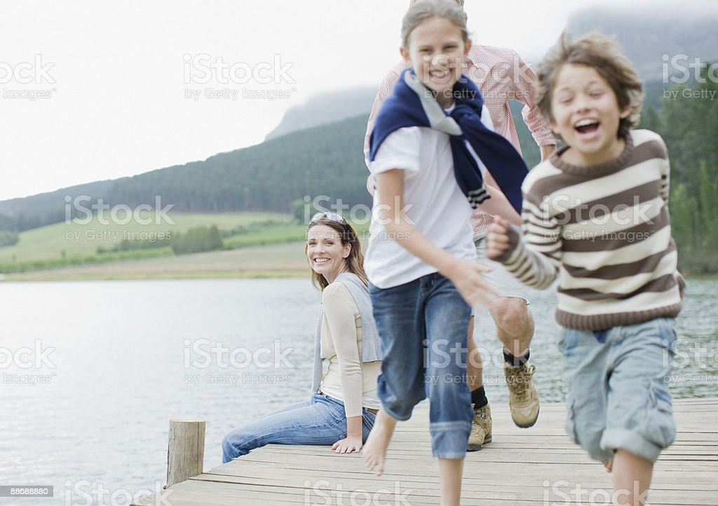 Children running on pier by lake stock photo