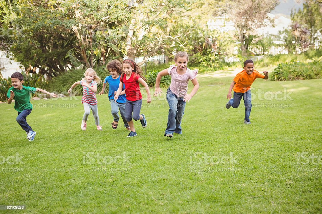 Children running on the grass stock photo
