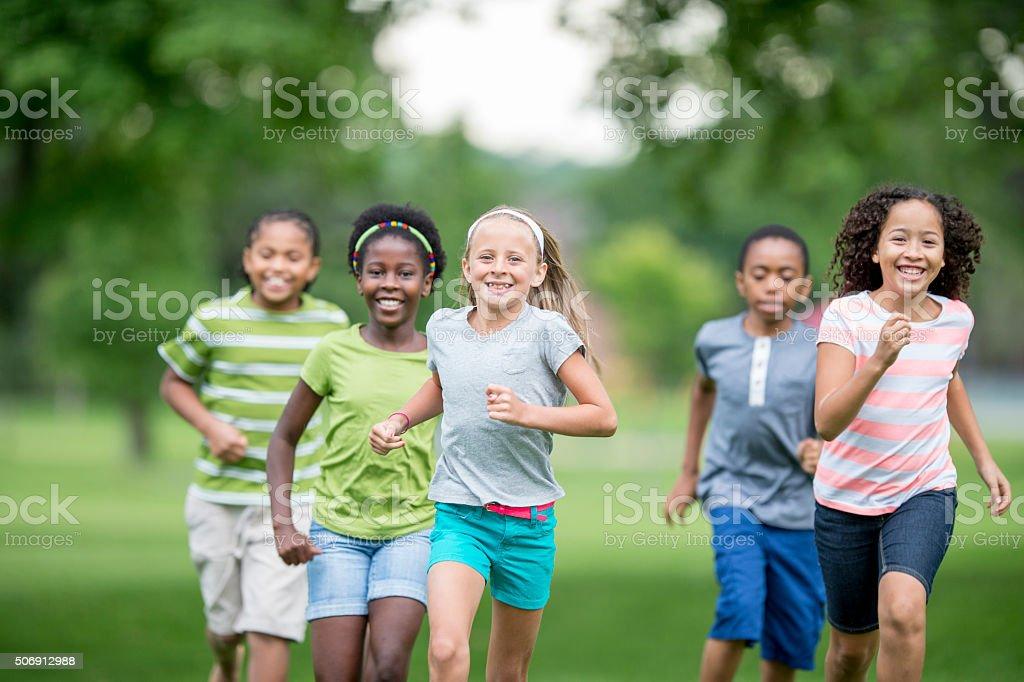 Children Running Through the Grass stock photo