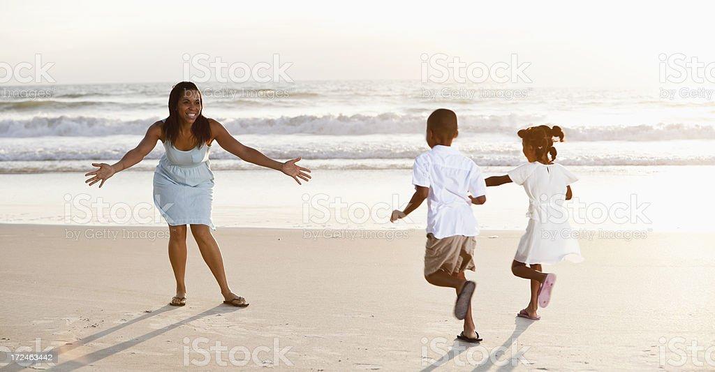 Children running to mother on beach stock photo