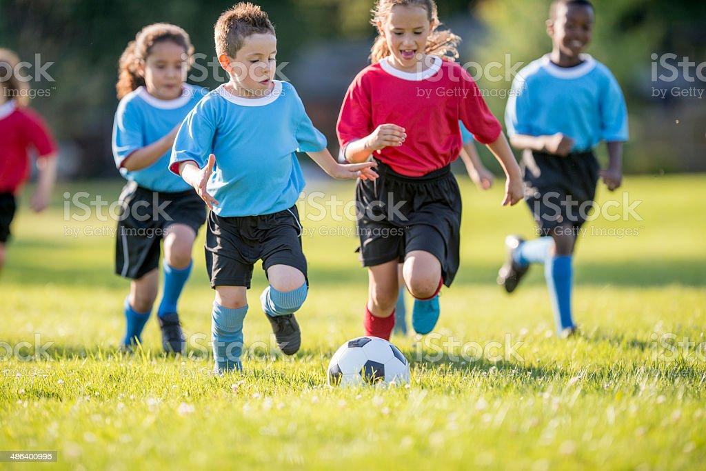 Children Rush to Soccer Ball stock photo