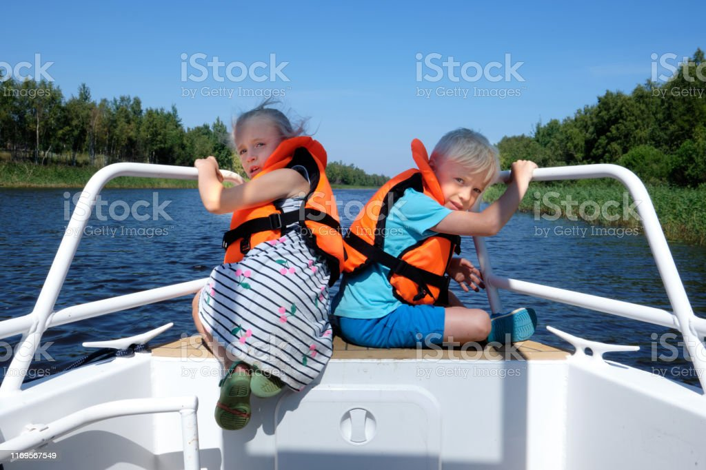 Children sail on a boat on the river. A little boy and girl in life...