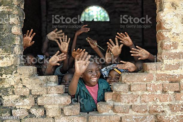 A group of african children inside of a destroyed school, wave hands and say hello.