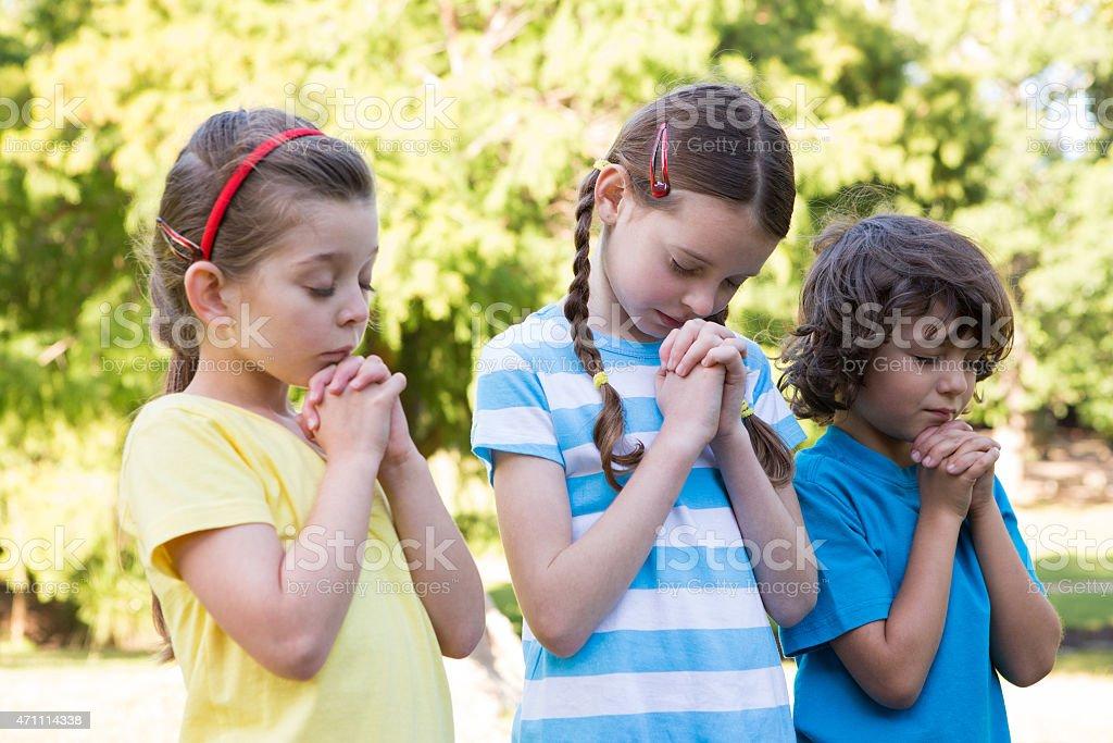 Children saying their prayers in park stock photo