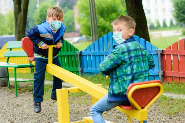 l'école d'enfants dans des masques médicaux jouent à une cour de récréation de quarantaine pendant une pandémie de coronavirus - masque enfant photos et images de collection