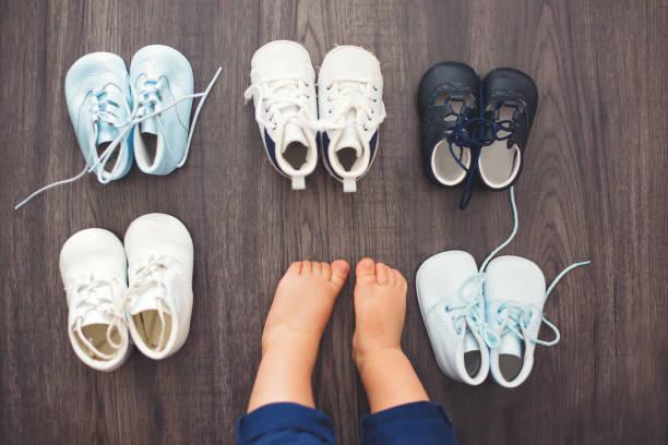 kinderschuhe und füße des babys auf einem hölzernen hintergrund - babyschuh stock-fotos und bilder