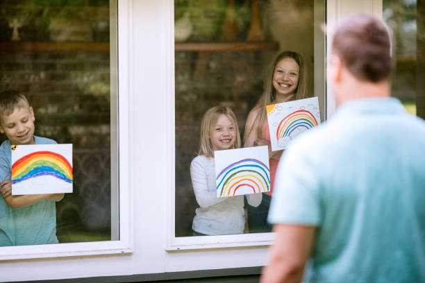 Children Show Rainbow Pictures Through Window to Family