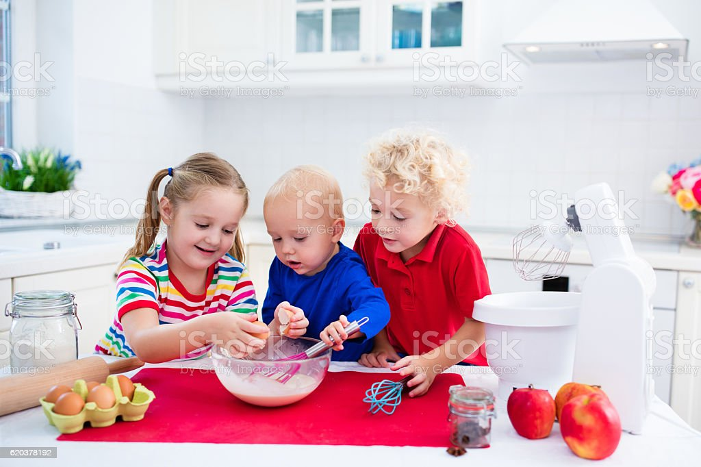 Children siblings baking a pie in white kitchen foto de stock royalty-free