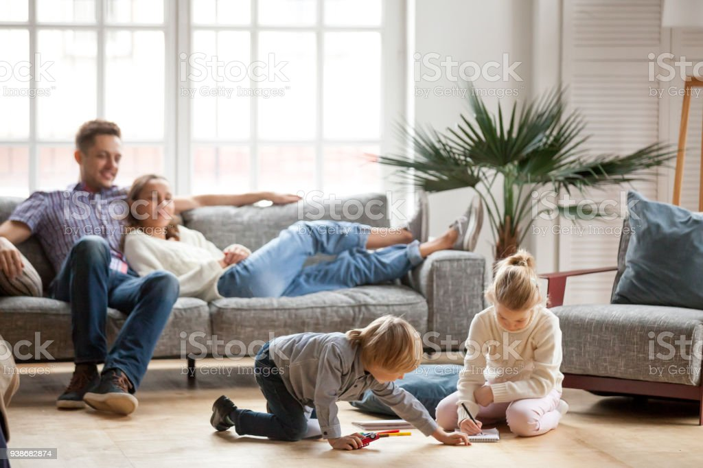 Children siblings playing drawing together while parents relaxing at home stock photo