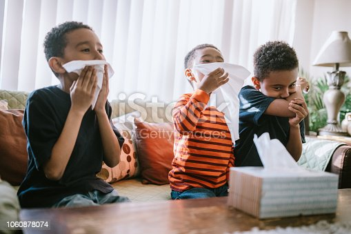 Three boys are sick at home, coughing and sneezing into tissues.   They rest on the couch while they recover from their illness.
