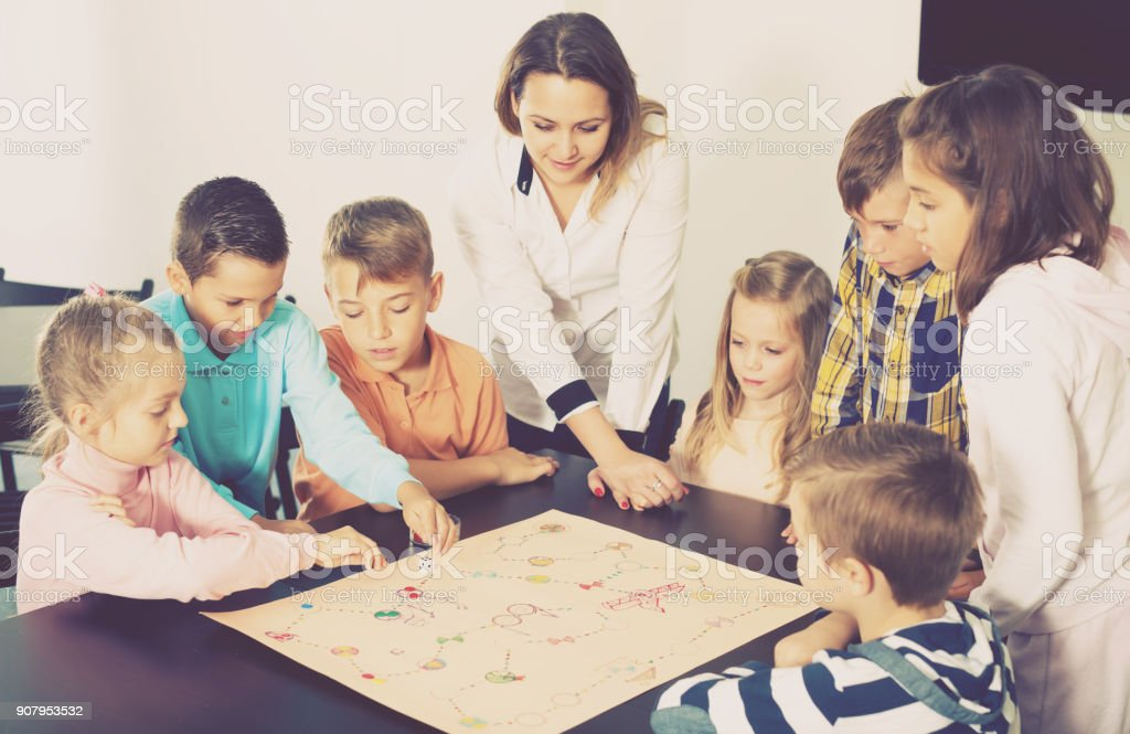 Woman and happy children sitting at table with board game and dice in...