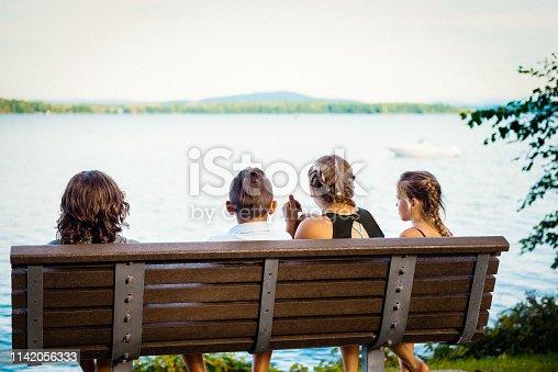 585604690 istock photo Children sitting in a bench park 1142056333