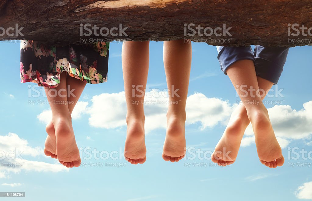 Children sitting in a tree dangling their feet stock photo