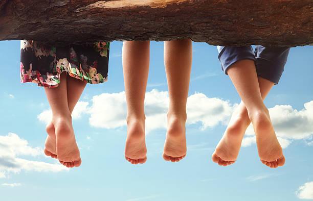 kinder sitzen auf einem ast baumelt ihre füße - kinderfüße stock-fotos und bilder