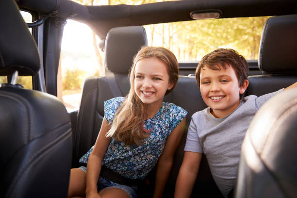 Children Sitting In Back Seat Of Open Top Car On Road Trip stock photo