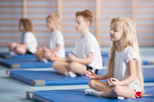 Group of children sitting in lotus pose on blue mats during yoga classes