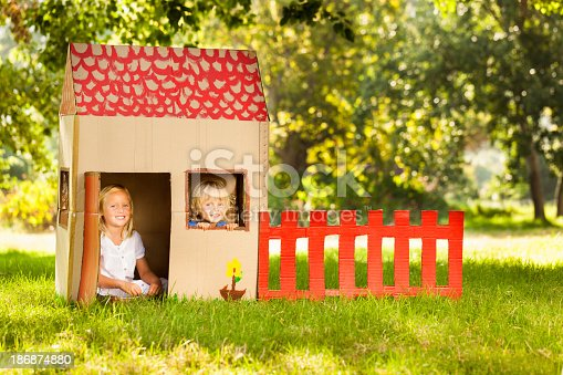 Portrait of happy little children sitting in playhouse. Horizontal Shot. Please checkout our lightboxes
