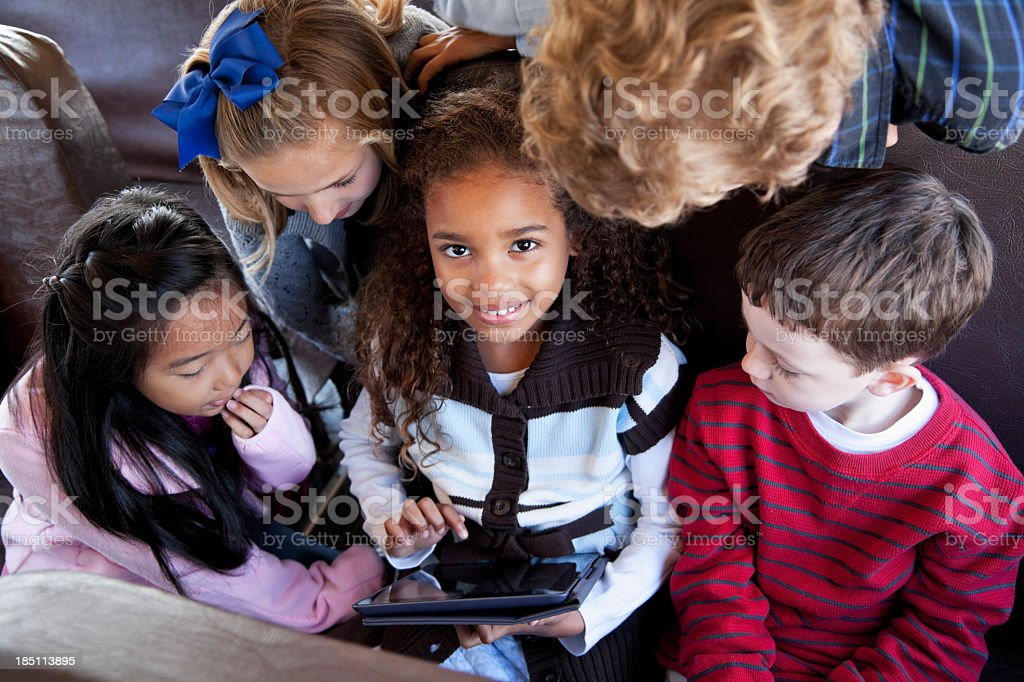Children sitting inside school bus with digital tablet stock photo