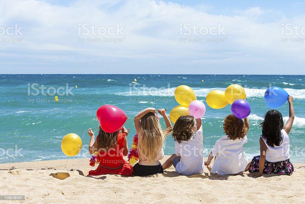 Enfants assis sur la plage avec des ballons de couleur. - Photo
