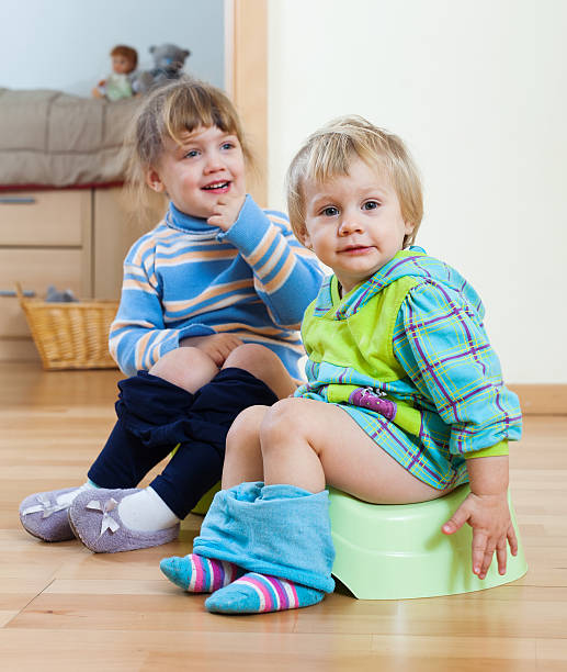 children  sitting on chamber pots stock photo