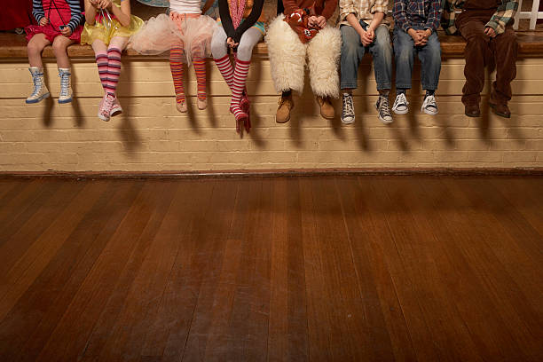 Children (5-12) sitting on edge of theatre stage, low section stock photo