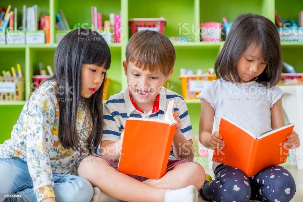 兒童坐在地板和閱讀故事書在學齡前庫中,幼稚園學校教育理念。圖像檔