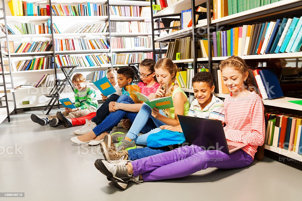 Children sitting on floor in library and studying stock photo
