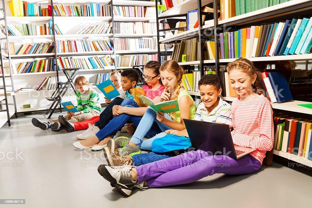 Niños sentado en el suelo y estudiando en la biblioteca - foto de stock