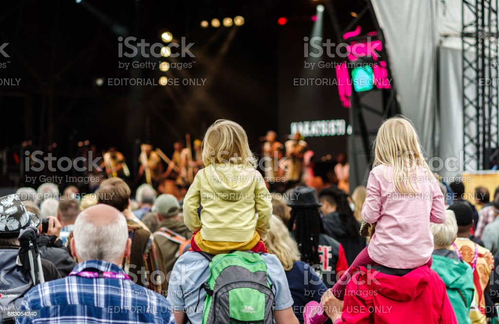 Children sitting on shoulders at festival stock photo