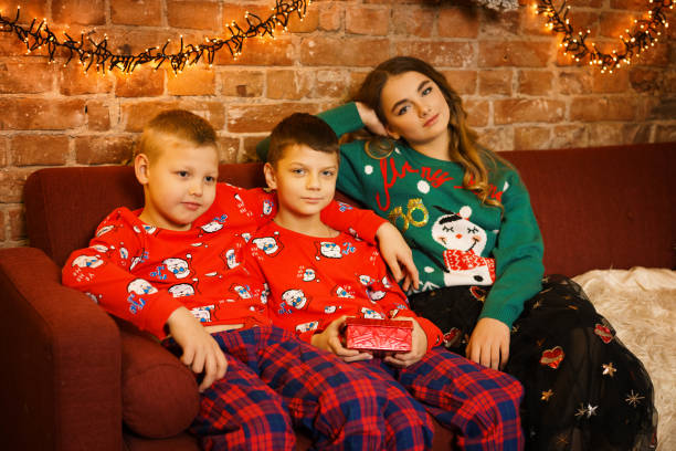 children sitting on the couch waiting for the new year stock photo