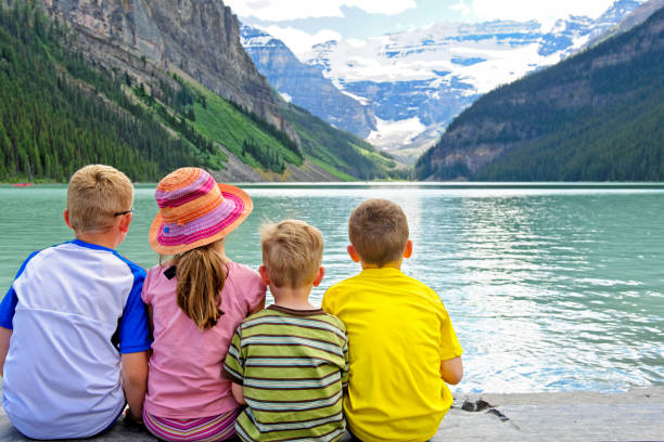 Children sitting on the edge of Lake Louise, Alberta,Canada stock photo