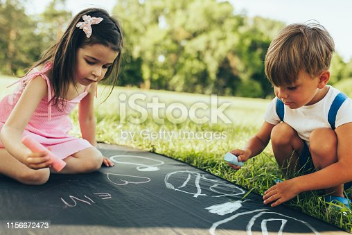 istock Children sitting on the green grass playing with colorful chalks. Happy two little kids drawing with chalks in the park. Two friends, boy and girl having fun on sunlight outdoors. Childhood 1156672473
