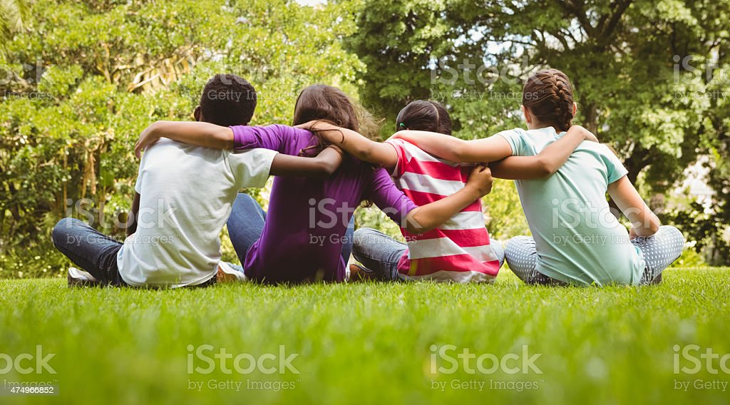 Children sitting with arms around at park stock photo