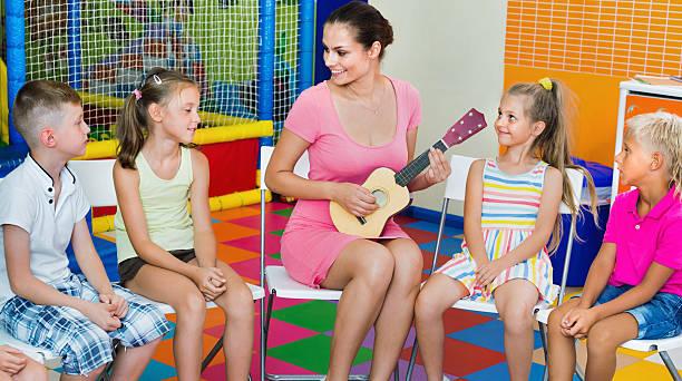children sitting with teacher and listening to music in class - ukulele songs stock-fotos und bilder