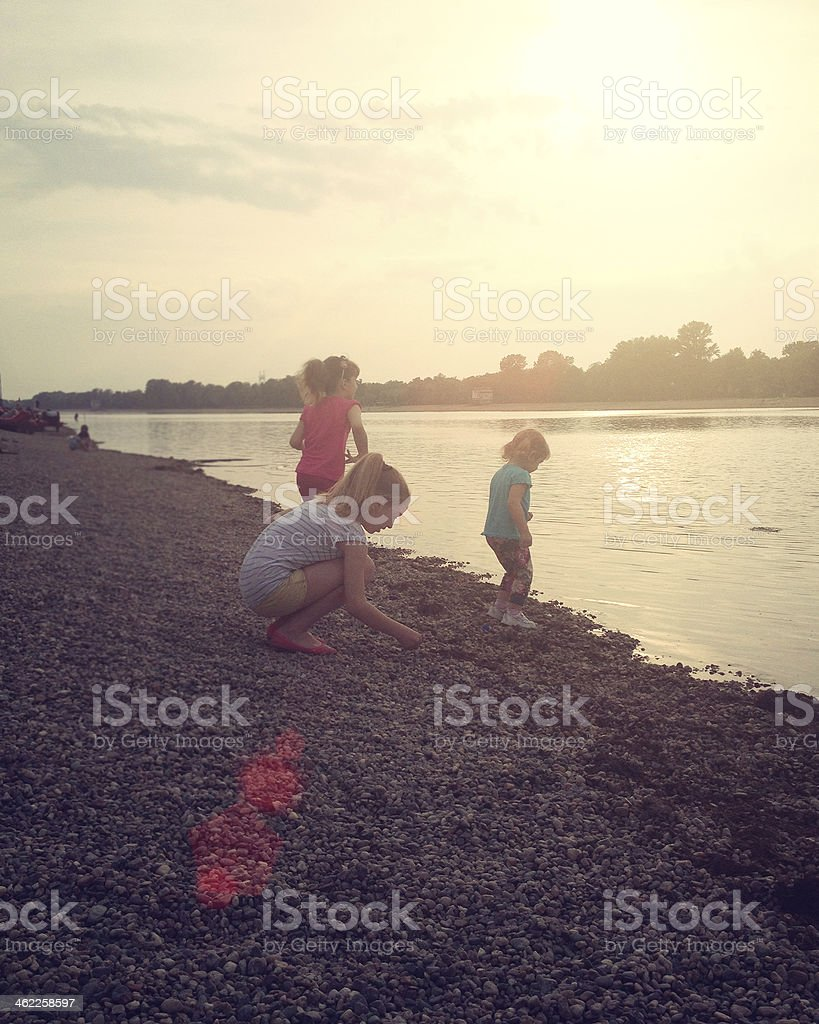 Children Skipping Stones at local lake. stock photo