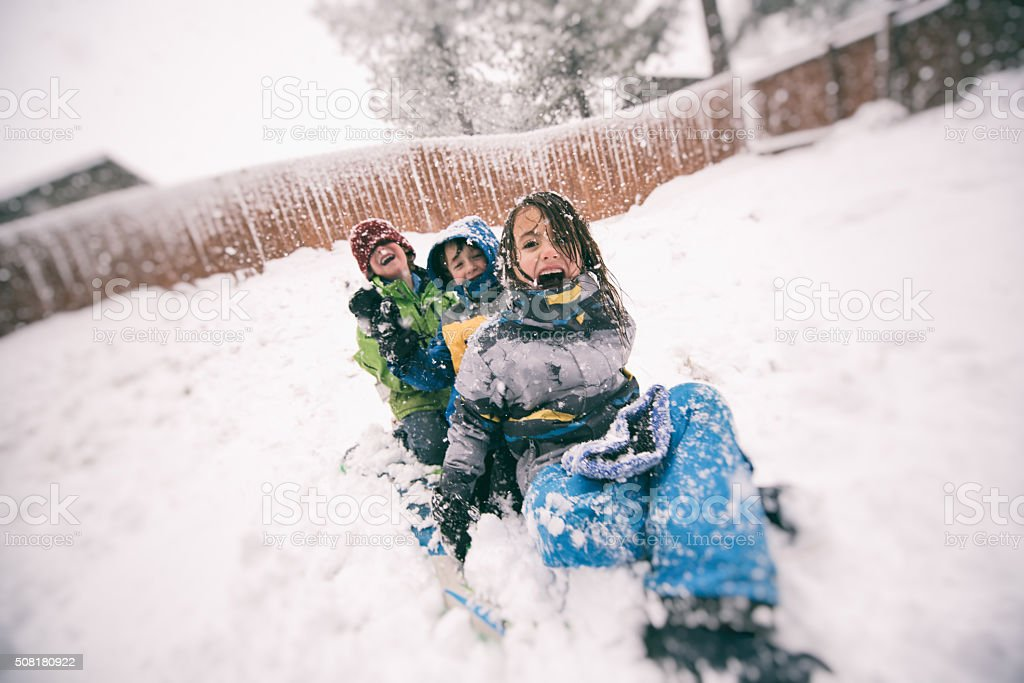 Children sled during a big winter snow storm stock photo