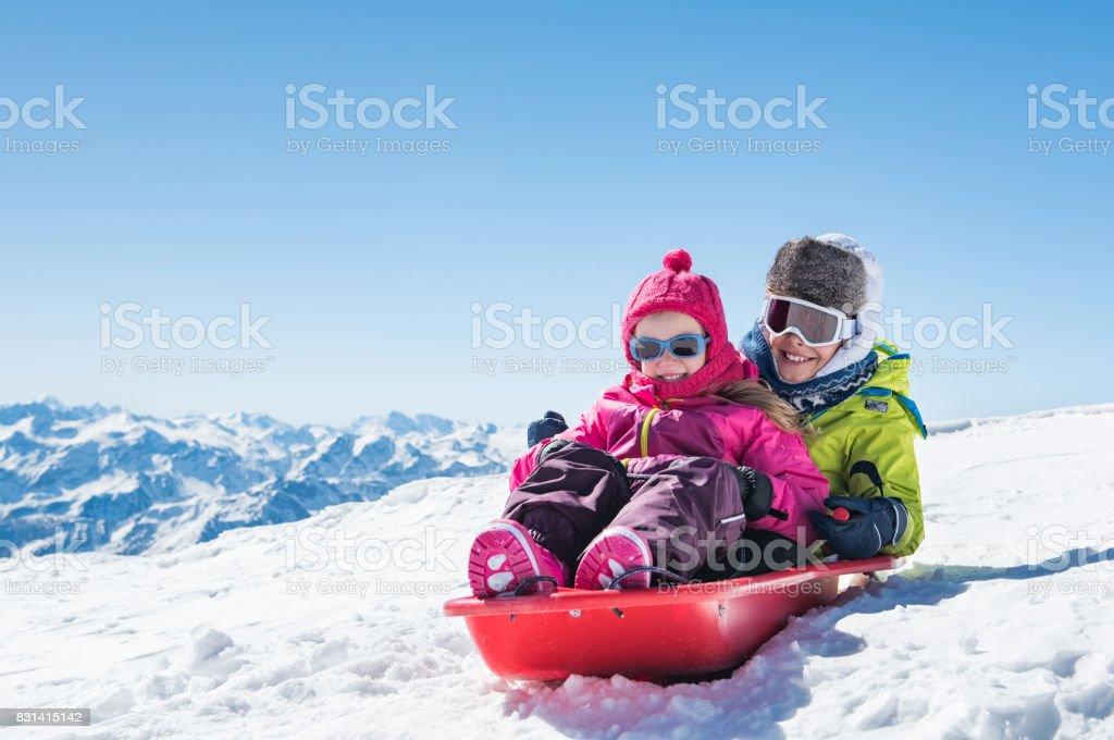 Children sledding on snow stock photo