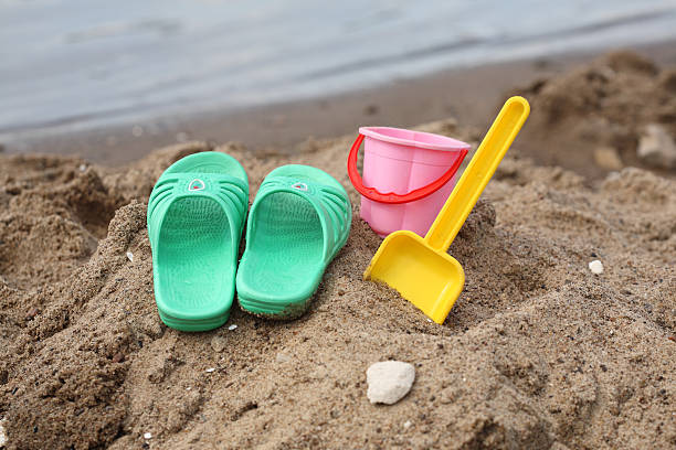 Children slippers and toys on beach stock photo
