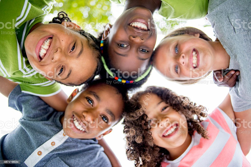 Children Smiling in a Huddle stock photo
