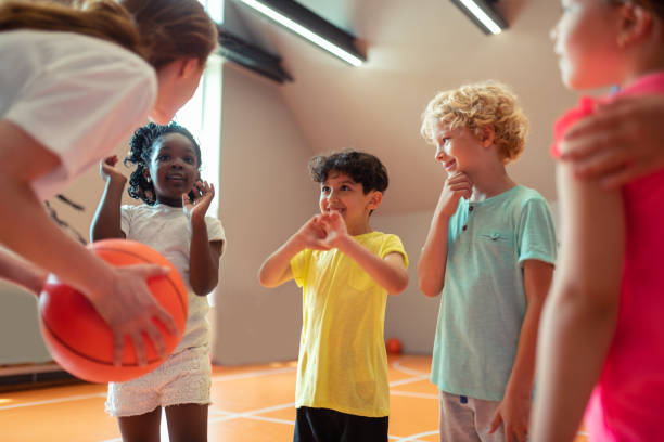 Children smiling to their sports teacher in the gym. stock photo